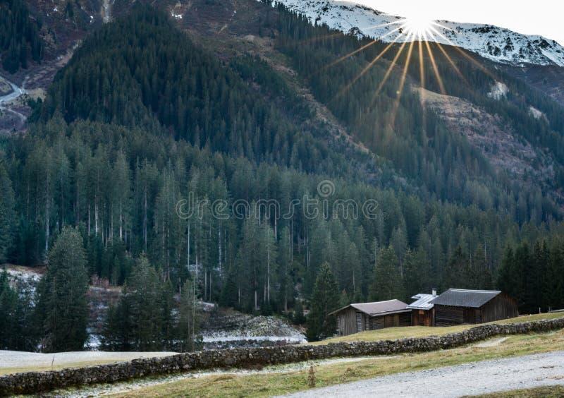 Berglandschap en vallei met bos en snow-capped bergpieken en een oude rotsmuur met houten erachter hutten en chalets royalty-vrije stock fotografie