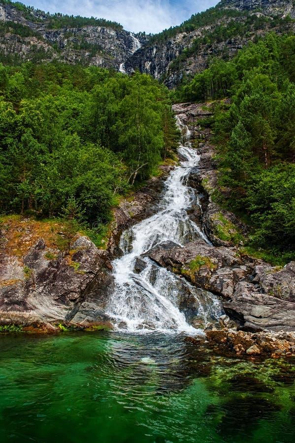 Berglandschap met een mooie waterval en een bewolkte hemel Mooie aard van Noorwegen De Geiranger-fjord royalty-vrije stock fotografie