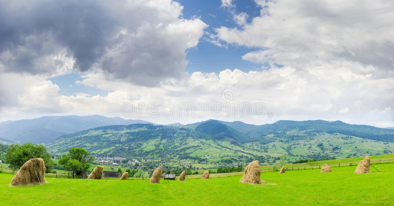 Berglandschap met hayfield op de voorgrond royalty-vrije stock foto