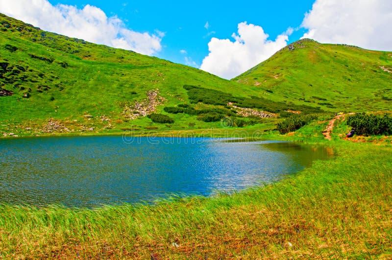 Berglandschap met meer en wolken in de hemel royalty-vrije stock foto