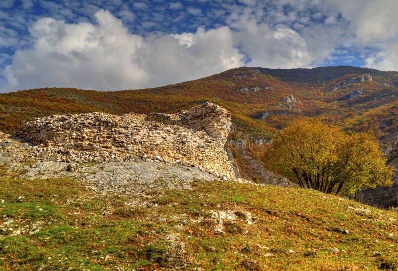 Berglandschap met ruïnes van oude vesting en kleurrijke de herfstbomen stock fotografie