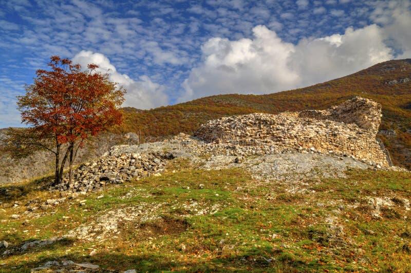 Berglandschap met ruïnes van oude vesting en kleurrijke de herfstbomen stock afbeeldingen