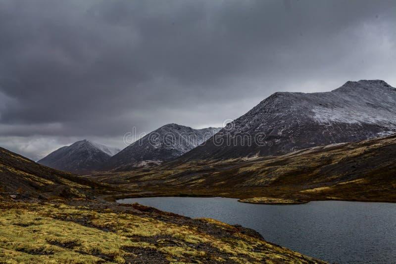 Berglandschap Rakkerland van een bergmeer op een regenachtige herfstdag Eerste sneeuw stock afbeelding