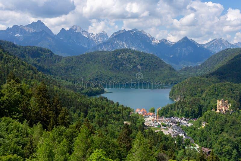 Berglandskap i de bayerska fjällängarna med byn Hohenschwangau, Bayern, Tyskland solig dagsommar arkivfoto