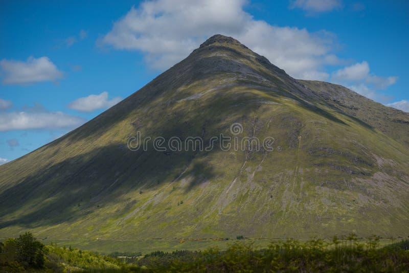 Berglandskap i det Glencoe området i Skottland, vårsiktsberg med grässlätten och bygdvägen i dalen av royaltyfri bild