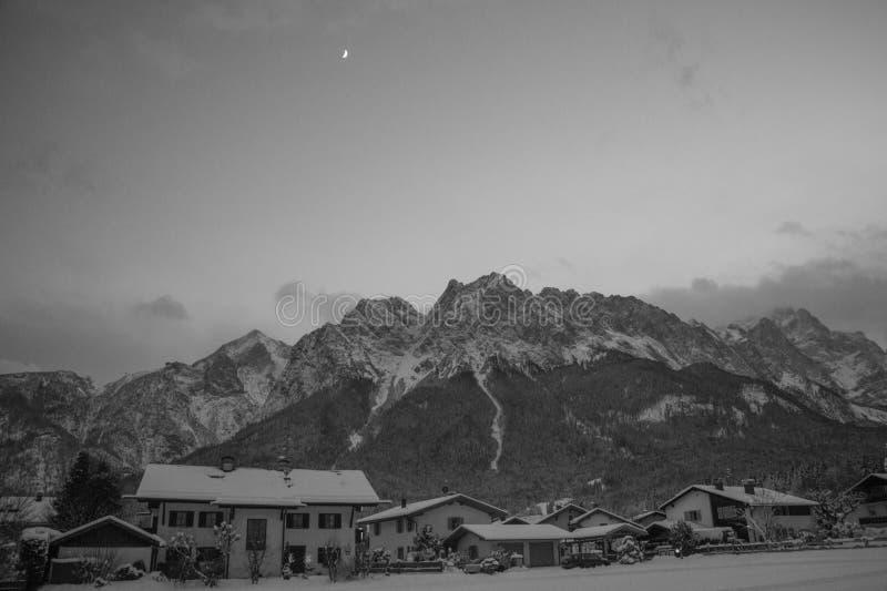 Berglandskap med den bergmassiven och byn i vintertid på natten royaltyfria bilder