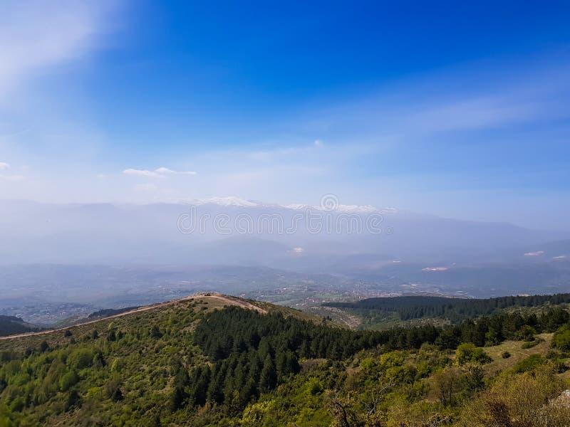 Berglandskap med gröna träd och blå himmel arkivfoto
