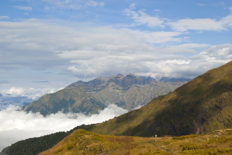 Berglandskap med moln och fotvandraslingan med en vägvisare royaltyfria foton