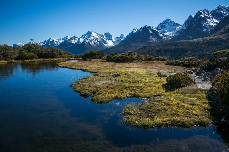 berglandskap med vatten i förgrund arkivfoton