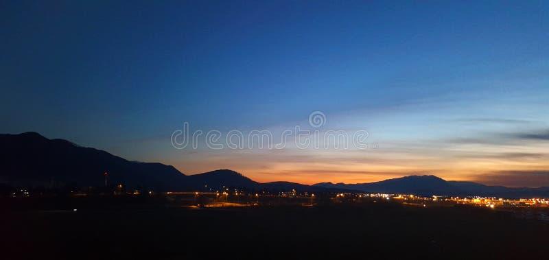 Berglandskap nära staden på nattetid fotografering för bildbyråer