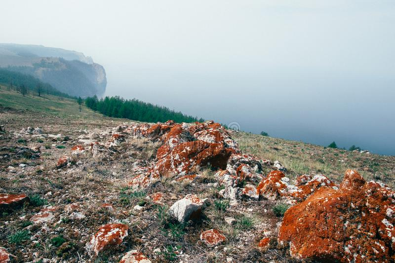Berglandskap och dimmig sjö arkivfoto