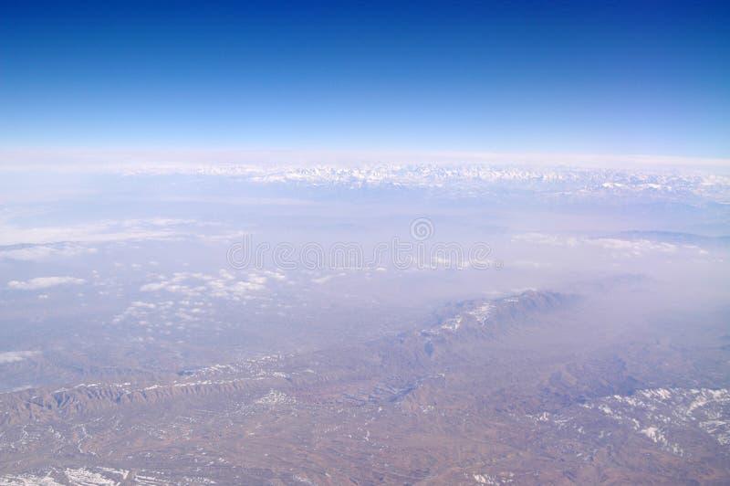 Berglandskap på blå himmel, flyg- sikt Jordyttersida Miljöskydd och ekologi reslust och lopp royaltyfri foto