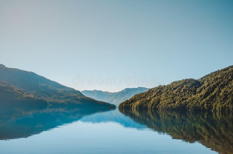 Berglandskap reflekterat i vattnet royaltyfri bild