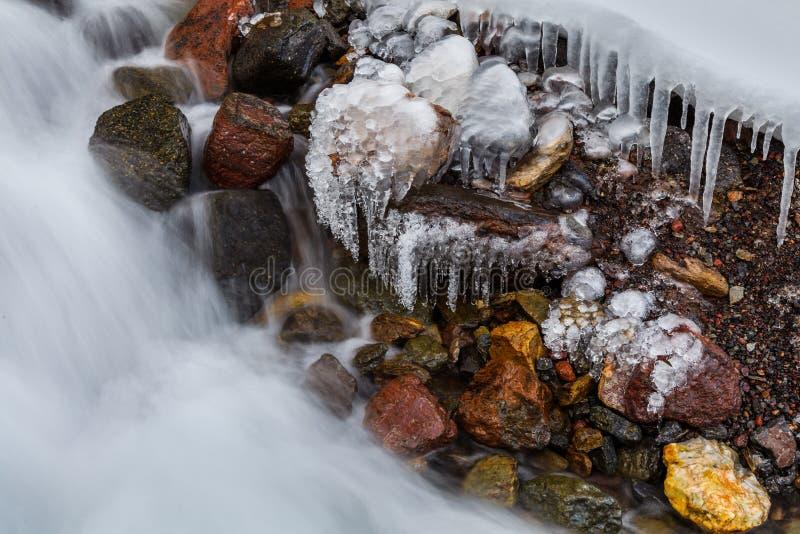 Bergliten vik med istappar och is vaggar på arkivbilder