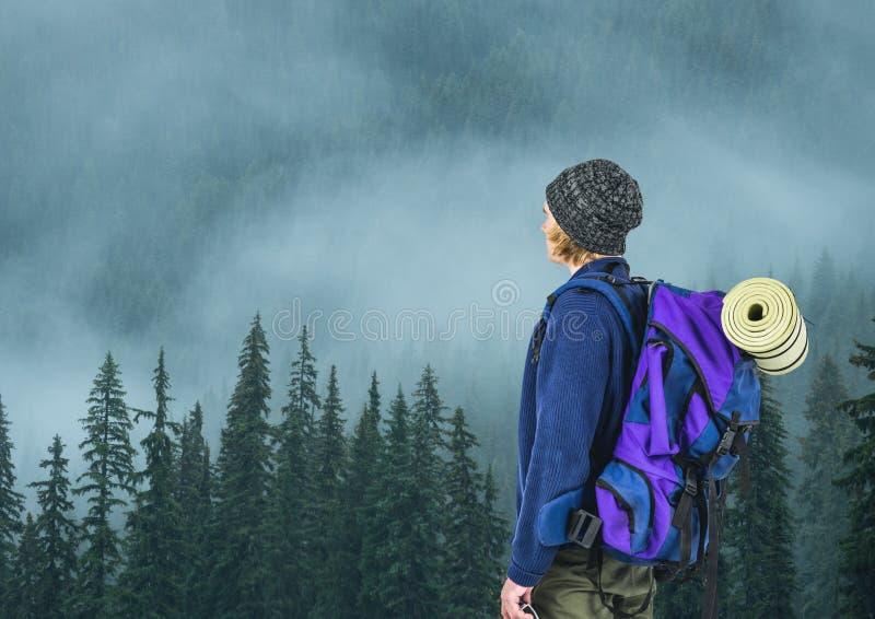 berglopp, unga blonda män med den gråa hatten nära skogen royaltyfria foton