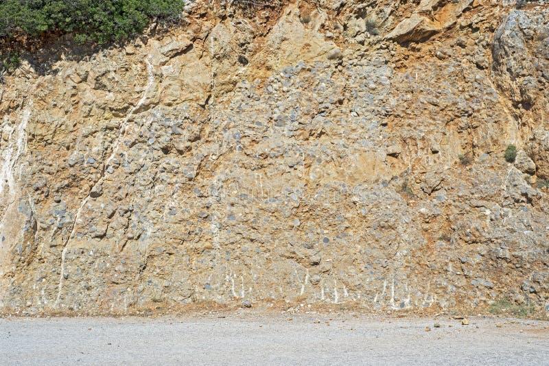 Berglutning nära den smutsiga sandiga vägen royaltyfria foton