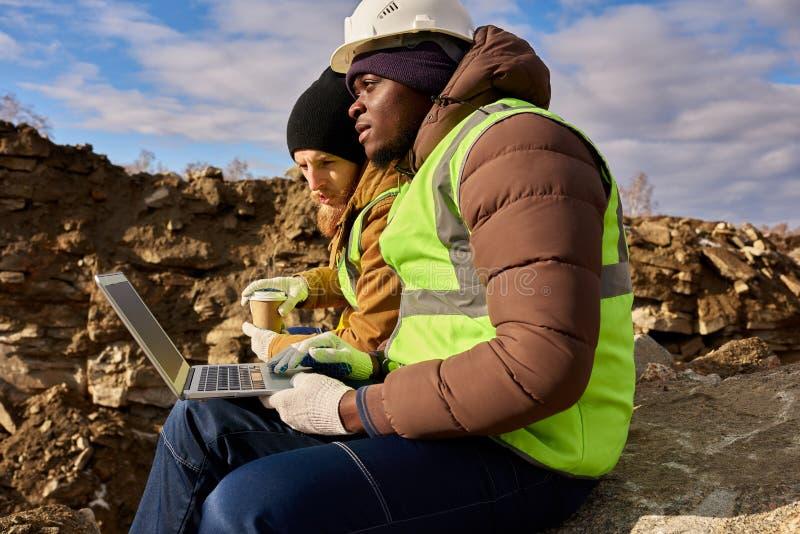 Bergmänner, die Laptop auf Aushöhlungs-Standort verwenden lizenzfreies stockfoto
