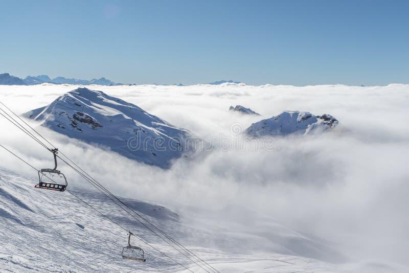 Bergmaxima som täckas i snö ovanför moln i La Plagne, franska savojkålfjällängar Sceniskt landskap för vinter, blå himmel och bed arkivfoto