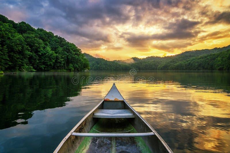 Bergmeer en kano bij zonsondergang stock afbeelding