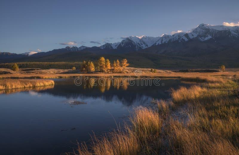 Bergmeer op een achtergrond van de herfstlandschap en sneeuw afgedekte bergen stock afbeelding