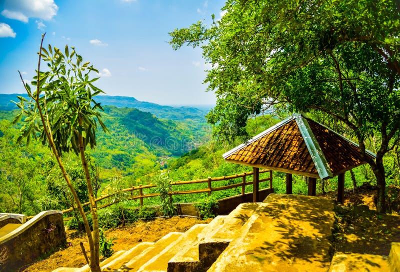 Bergmening van een rust hut met weelderige groene bos en gele rivier in Oost-Azië stock fotografie