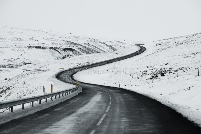 Bergopwaarts weglandschap in de winter in IJsland Asfaltweg met zijdelings volledig van sneeuw stock foto