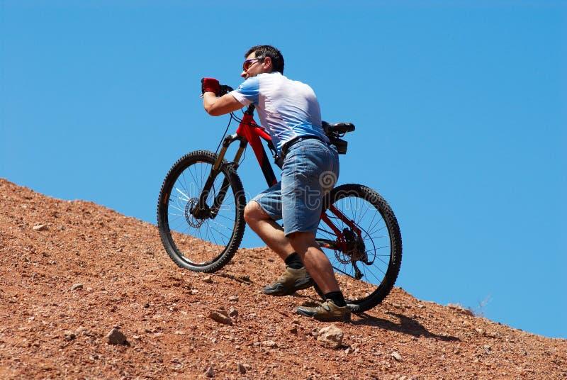 Bergopwaartse de fietser van de berg stock afbeeldingen