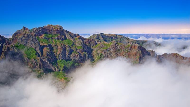Bergpieken in de wolken tegen blauwe oranje hemel Het Eiland van madera stock fotografie