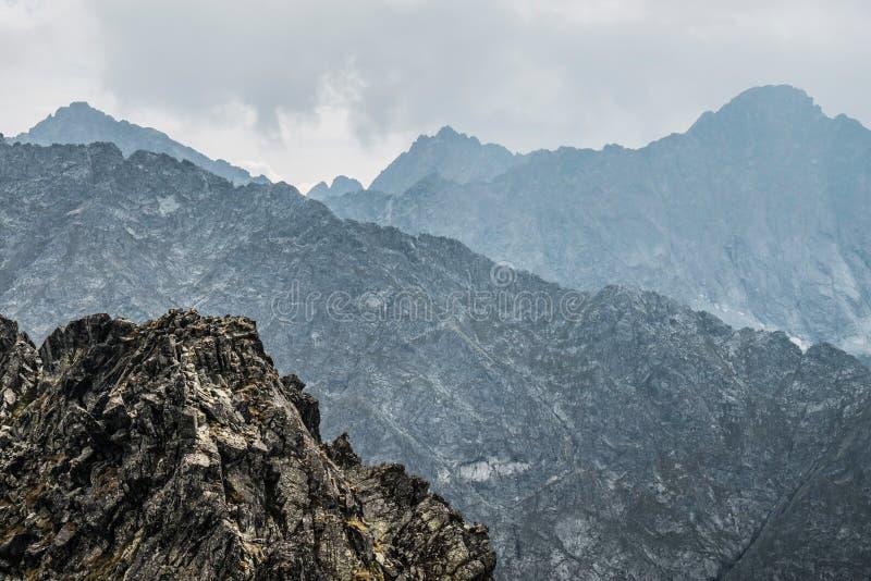 Bergpieken gebaad in wolken stock afbeeldingen