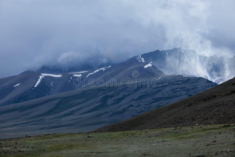 Bergpieken in sneeuw en een fantastische vulkaan met stea worden behandeld die stock afbeelding