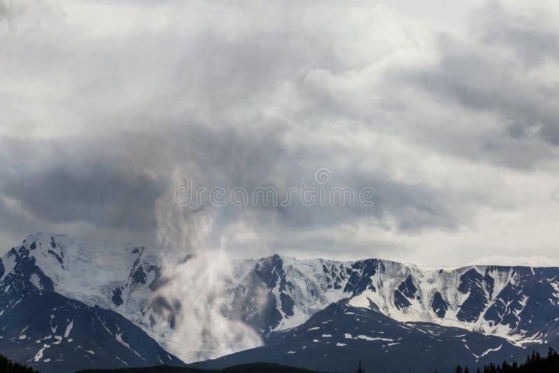 Bergpieken in sneeuw en een fantastische vulkaan met stea worden behandeld die stock fotografie