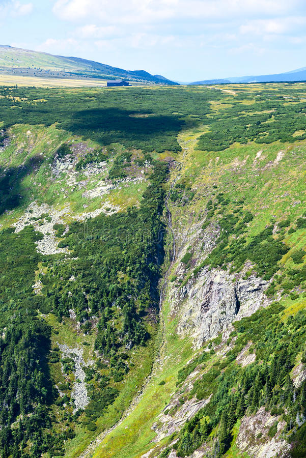 Bergplateau die neer aan een diepe vallei met een waterval vallen royalty-vrije stock foto's