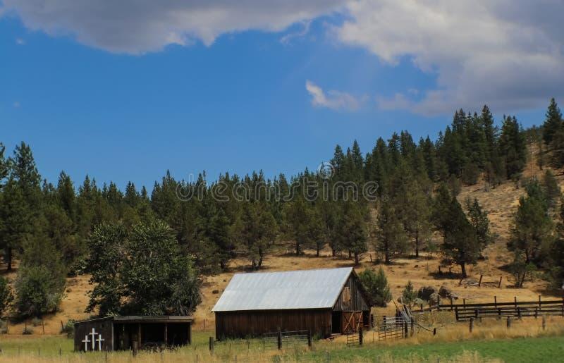 Bergplats med ladugården och ladugården med kristenkors som visas mot pinecovered kullar och en blå himmel med moln royaltyfria foton