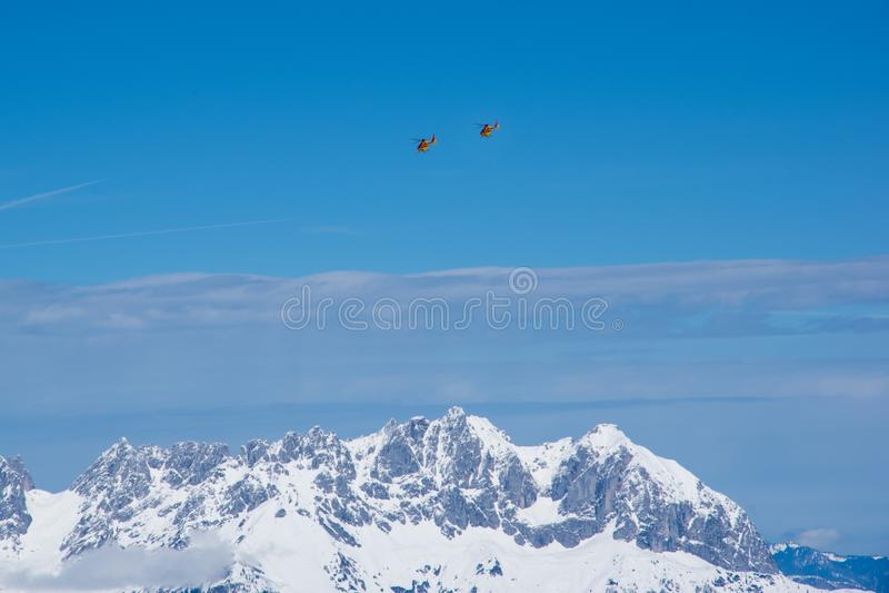 Bergräddningsaktionhelikoptrar ovanför fjällängar, Kitzbuhel, Österrike fotografering för bildbyråer