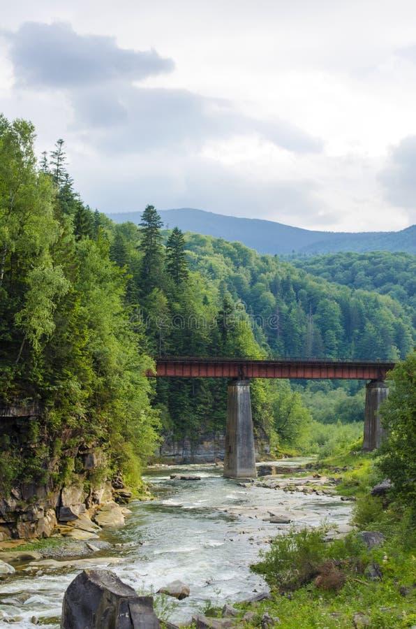 Bergrivier met een snelle stroom van rotsen en een brug royalty-vrije stock foto