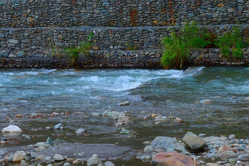Bergrivier met steenbanken, borrelende stroom van water stock afbeelding