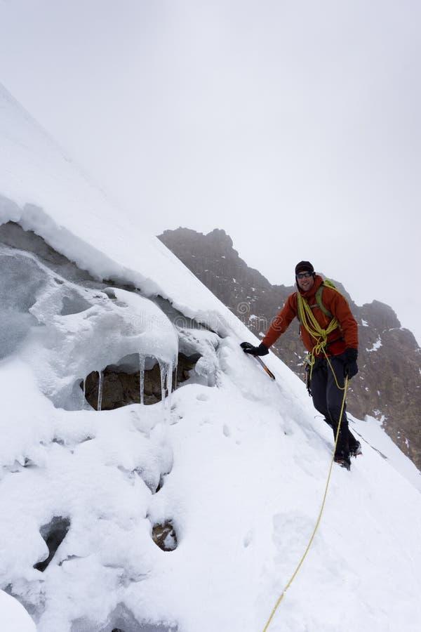 Bergsbestigare i ett rött omslag på en brant glaciär i Anderna i Peru royaltyfri foto