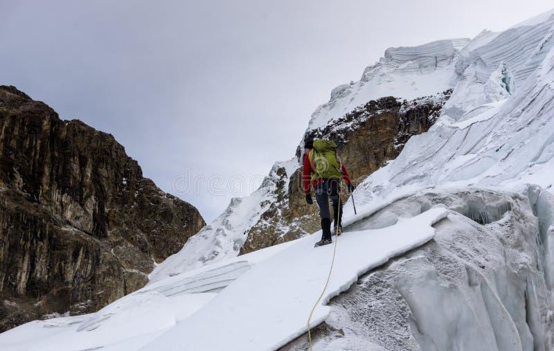 Bergsbestigare i ett rött omslag på en brant glaciär i Anderna i Peru royaltyfria foton