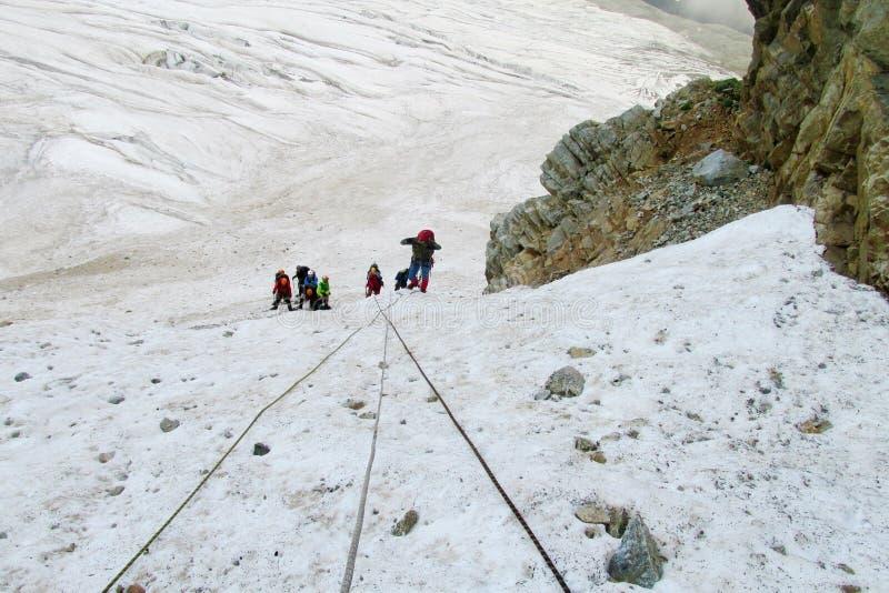 Bergsbestigare med rep på snö arkivbild