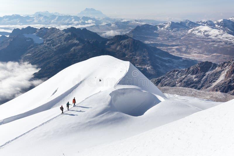 Bergsbestigare som går klättringsnö, skuggar bergkanten, Bolivia royaltyfri foto
