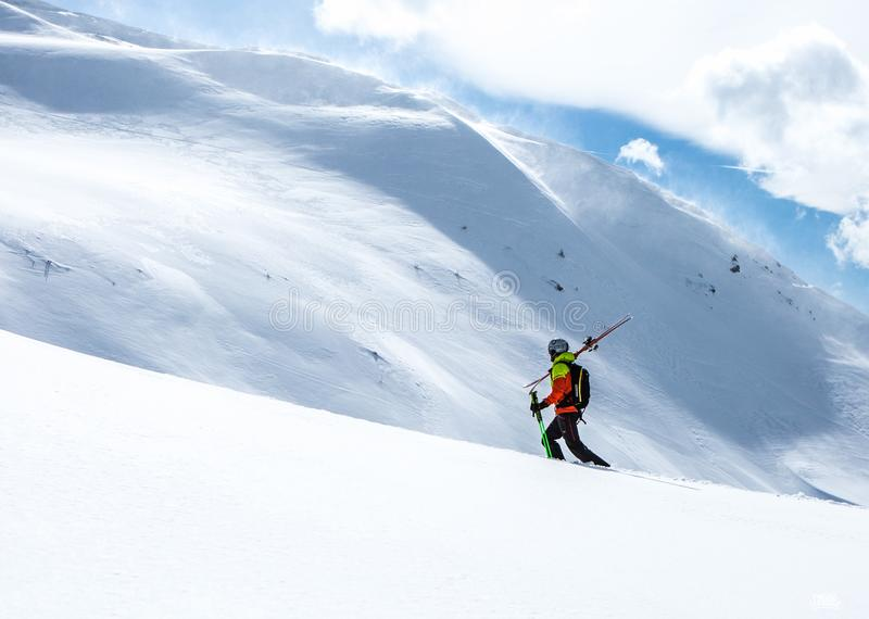 Bergsbestigare som går upp längs en snöig kant I bakgrund en skinande ljus sol arkivfoton