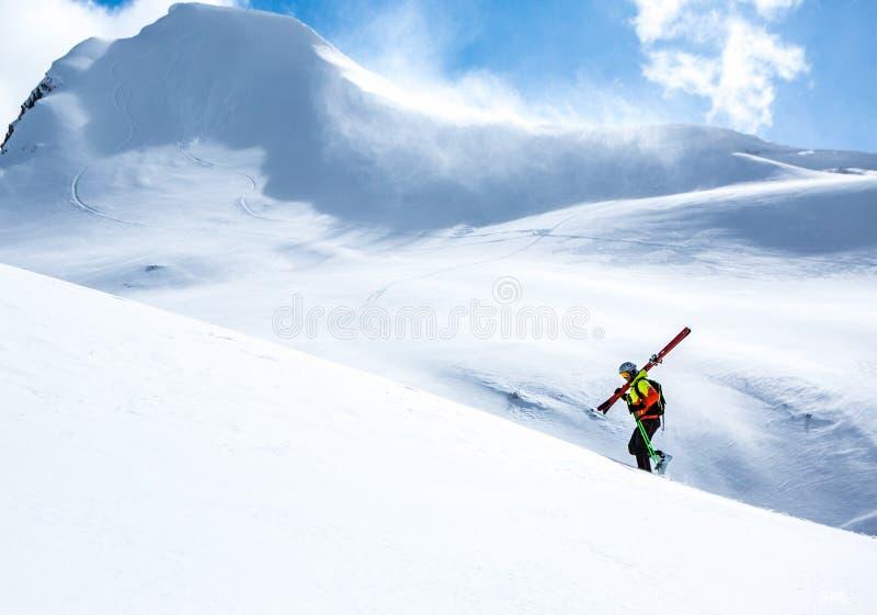 Bergsbestigare som går upp längs en snöig kant I bakgrund en skinande ljus sol arkivfoto