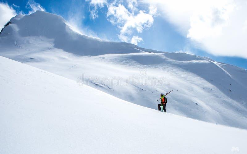 Bergsbestigare som går upp längs en snöig kant I bakgrund en skinande ljus sol royaltyfri foto