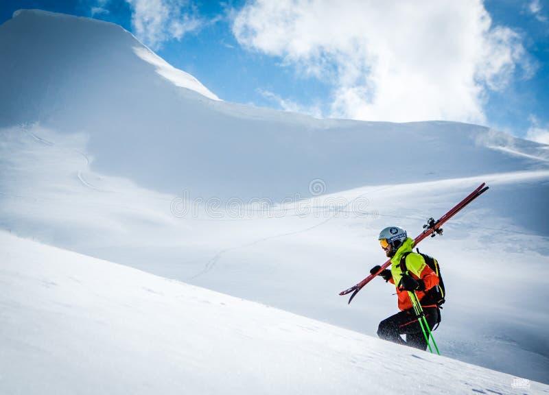 Bergsbestigare som går upp längs en snöig kant I bakgrund en skinande ljus sol fotografering för bildbyråer
