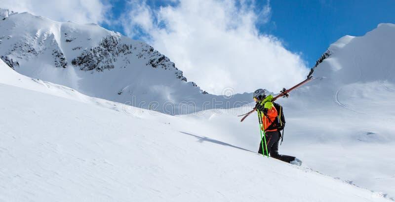 Bergsbestigare som går upp längs en snöig kant I bakgrund en skinande ljus sol royaltyfri bild