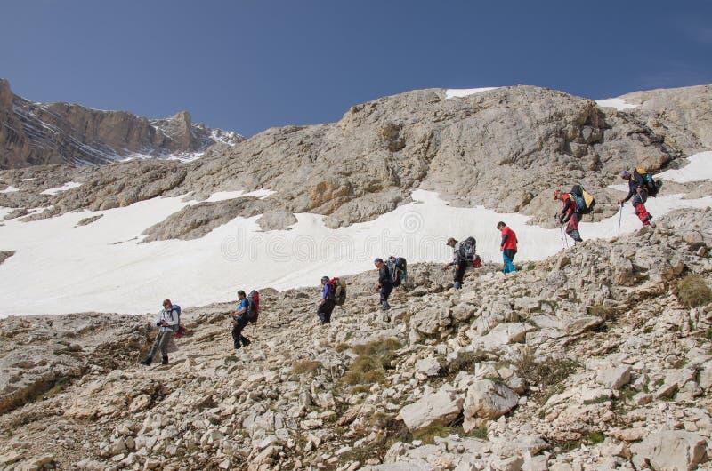 Bergsbestigare som stiger ned längs den steniga banan royaltyfri bild
