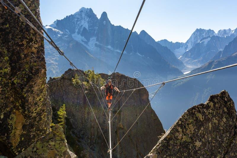 Bergsbestigarekorsning kabelbro via ferrataen, Chamonix France arkivfoto