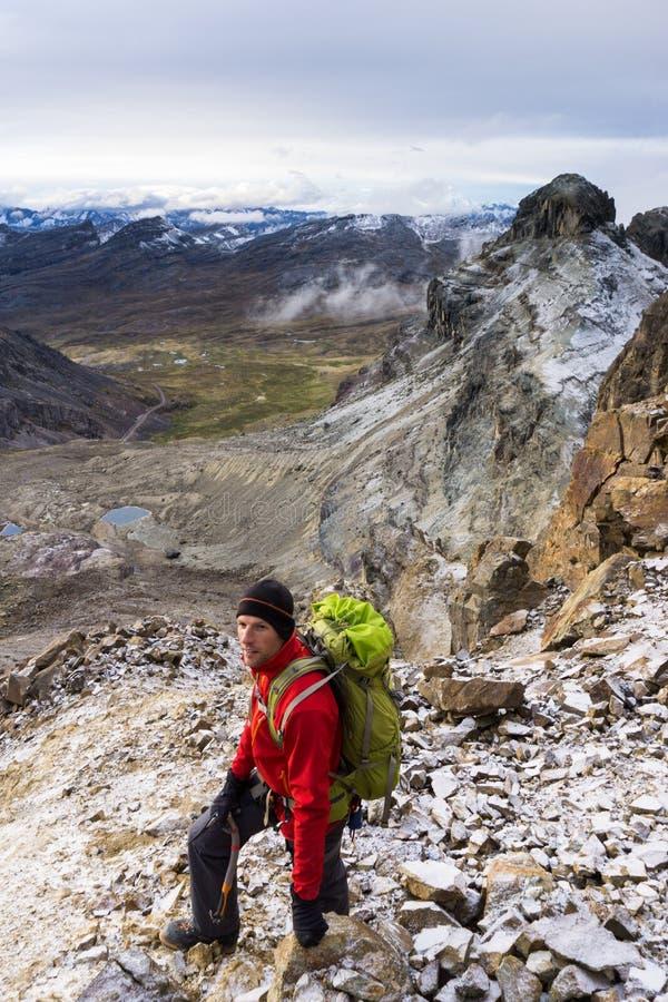 Bergsbestigaren i ett rött omslag på ett brant vaggar lutningen i Anderna i Peru royaltyfria foton