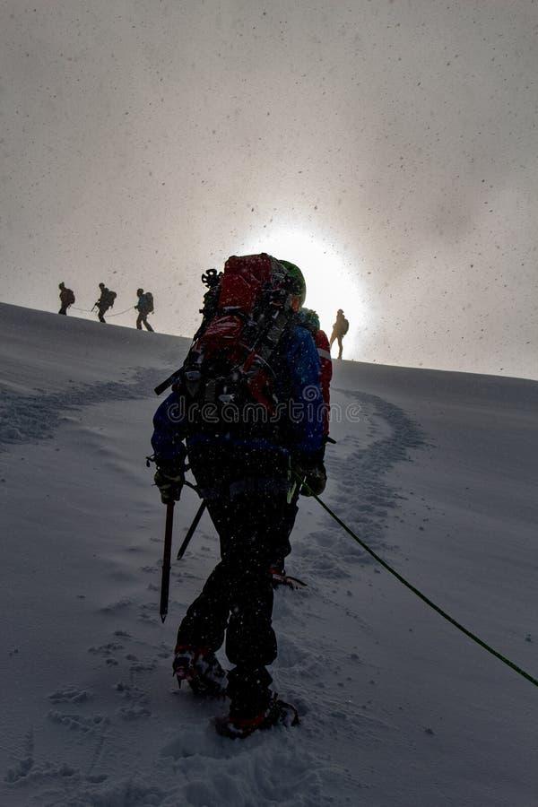 Bergsbestigaren i soluppgång på en snöig stigning på ett alpint turnerar kallade Spagetti Runda i de europeiska fjällängarna, Mon royaltyfri bild