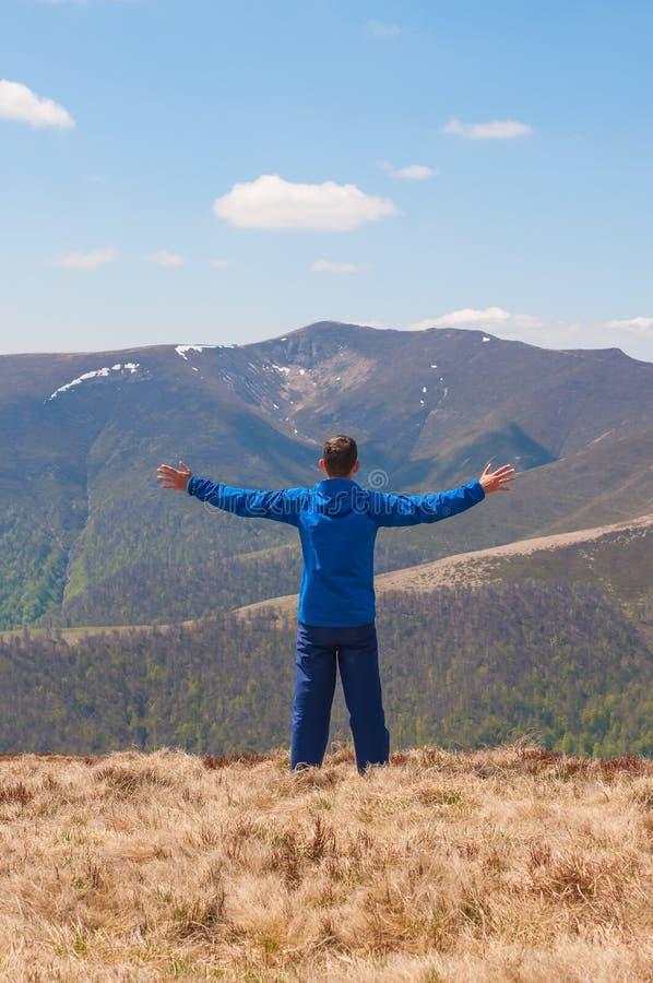Bergsbestigaren når överkanten av ett berg i soligt arkivbild